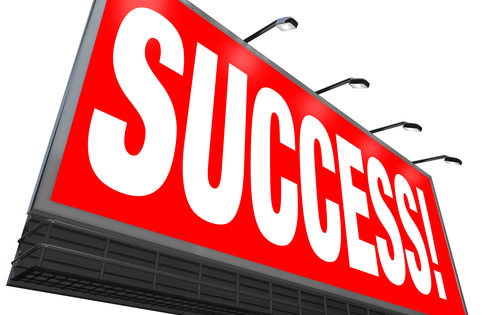 The word Success on a red outdoor billboard advertising a successful answer or solution for your goal or challenge